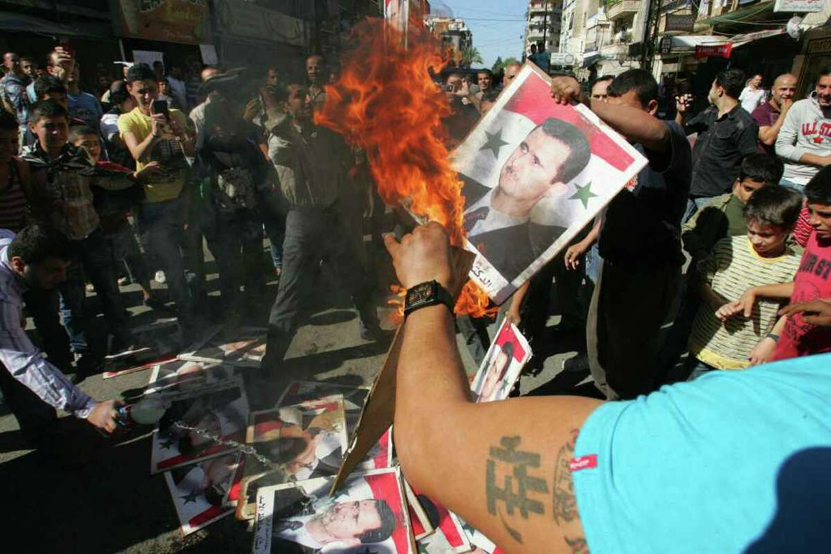 Protesters burn portraits of Syria's President Bashar al-Assad during a rally in the Lebanese city of Tripoli in October.