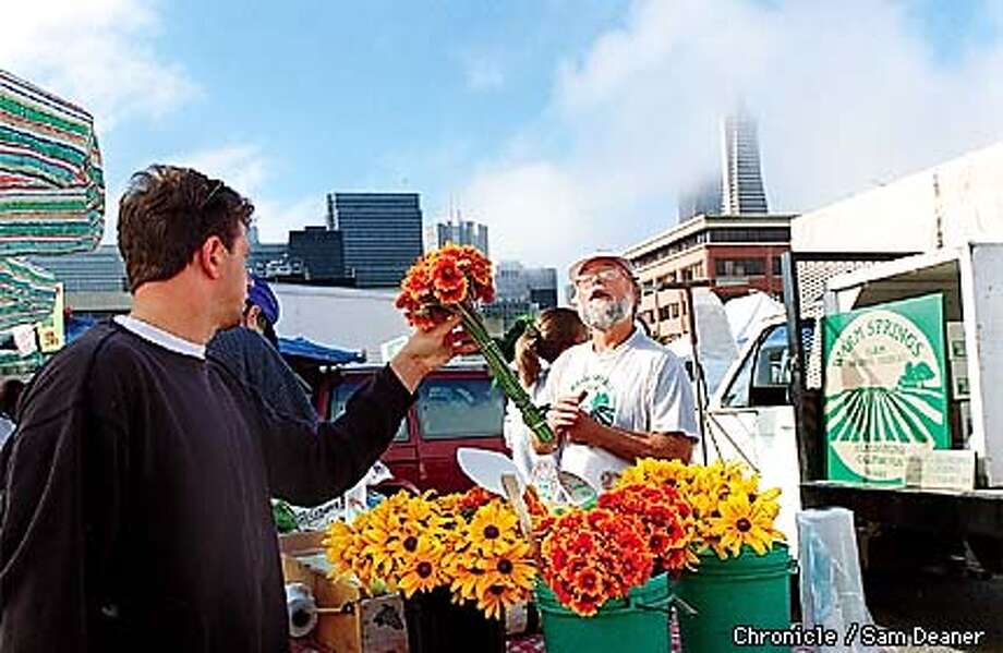 Healdsburg organic farmer Larry Tiller sells a bouquet of flowers to Gregg Kofman of San Francisco who inquires about the price at Tiller's stand at the Ferry Plaza Farmer's Market in San Francisco Saturday. (CHRONICLE PHOTO BY SAM DEANER) Photo: SAM DEANER