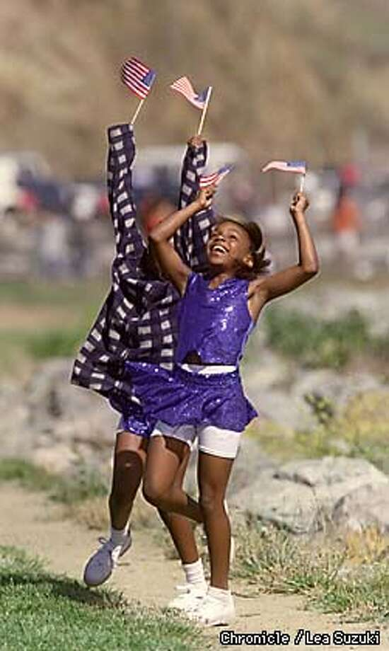 From right: Alexis Brown, 9, and Jalesse Clark, 10, both of Richmond, dance at the water's edge in Point Richmond waving a welcome with their flags as the Red Oak arrives in Richmond. Photo By Lea Suzuki Photo: LEA SUZUKI