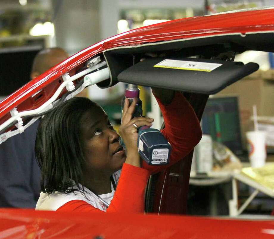 An auto worker assembles parts on the 2013 Dodge Dart at the Chrysler Plant in Belvidere, Ill., Thursday, Feb. 2, 2012. Sergio Marchionne, Chairman and CEO Chrysler Group, announced that Chrysler will add a third shift at the Belvidere Plant to begin production of the Dart. The unemployment rate fell for the fifth straight month after a surge of January hiring, a promising shift in the nation's outlook for job growth. (AP Photo/Charles Rex Arbogast) Photo: Charles Rex Arbogast / AP