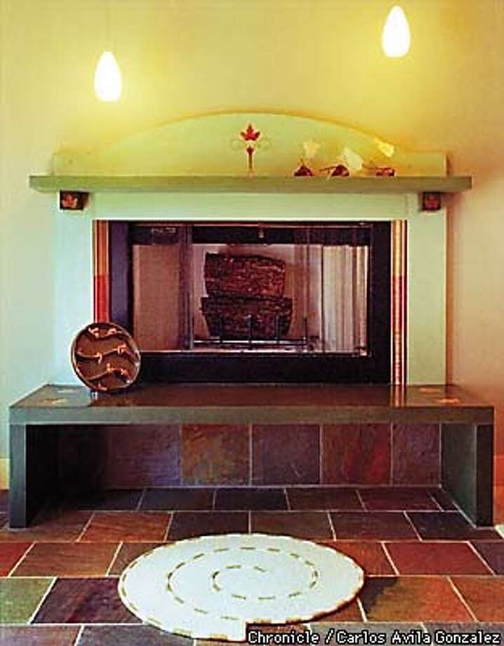Hand crafted concrete fireplace with inset tile and maple leaf accents. The fireplace is in designer Sherry Scott's home in Redwood City, and was created by Mat Rogers of Flying Turtle Concrete of San Francisco. The fireplace is encircled by a slate-paved floor. BY CARLOS AVILA GONZALEZ/THE CHRONICLE Photo: CARLOS GONZALEZ