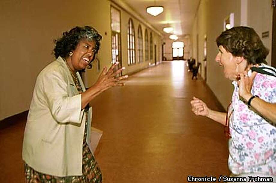 Sylvia Davis, left and Eileen Suzio break into song, harmonizing the pep song of their alma mater, University High School. Both women are graduates of the school who are planning to attend the grand opening of the North Oakland Senior Center on Thursday. (CHRONICLE PHOTO BY SUSANNA FROHMAN) Photo: SUSANNA FROHMAN