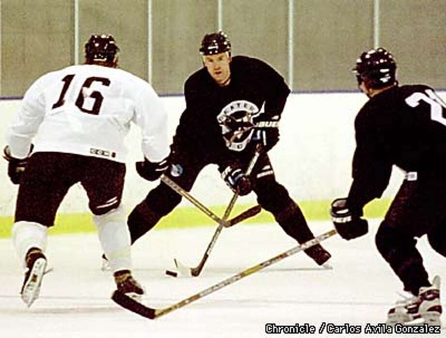 The Sharks' Bob Rouse,(3), works the puck past Alex Hicks, (16), during a scrimmage at the San Jose Ice Centre on Tuesday, September 15, 1998. (CHRONICLE PHOTO BY CARLOS AVILA GONZALEZ) Photo: CARLOS AVILA GONZALEZ