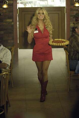 In an undated  handout photo from Pizza Hut, singer/actress Jessica Simpson carries a pizza with Cheesy Bites. Super Bowl ads are on the way. Forget about which Super Bowl team to root for. The biggest game-day decision for many armchair quarterbacks is deep dish or thin crust. On a day when pigskin partying hits its peak, Super Bowl Sunday has become a bonanza for the $37 billion pizza industry.   (AP Photo/Pizza Hut, Prashant Gupta) Photo: Prashant Gupta