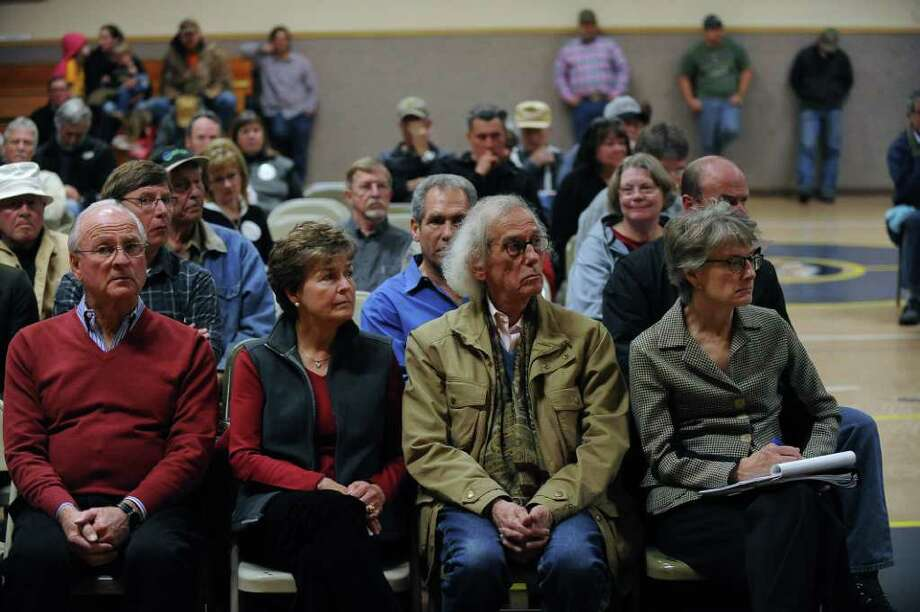 The artist Cristo sits with his Over the River team members as they listen to residents talk about the proposed project Thursday Feb. 2, 2012.  An open forum was held in front of the Fremont County Commissioners to listen to the opinions of residents in the area to the proposed project.  Seated next to Cristo, who is second from right, are Vince and Juanita Davenport, and Lori Potter, right.  The forum was held in the Cotapaxi school.The Over the River project proposes hanging aluminum coated material over 5.9 miles of the Arkansas River in scattered sections of over a 42 mile stretch. (AP Photo/Helen H. Richardson, The Denver Post) Photo: Helen H. Richardson / (C) 2011 The Denver Post, MediaNews Group