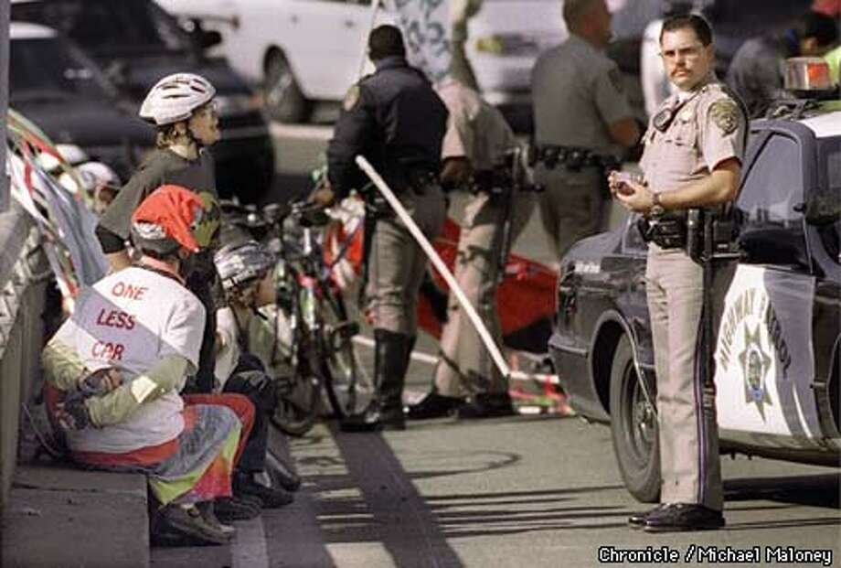 Bike protesters wait in handcuffs on the Fremont Street offramp of the Bay Bridge after being arrested for biking in the upper deck.  BY MICHAEL MALONEY/THE CHRONICLE Photo: MICHAEL MALONEY
