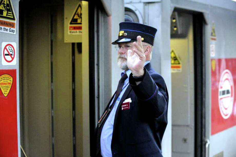 Conductor Howard Stephens signals to close the doors on the 7:10 a.m. train at the Branchville train station in Ridgefield Friday, Feb. 3, 2012. Photo: Michael Duffy / The News-Times