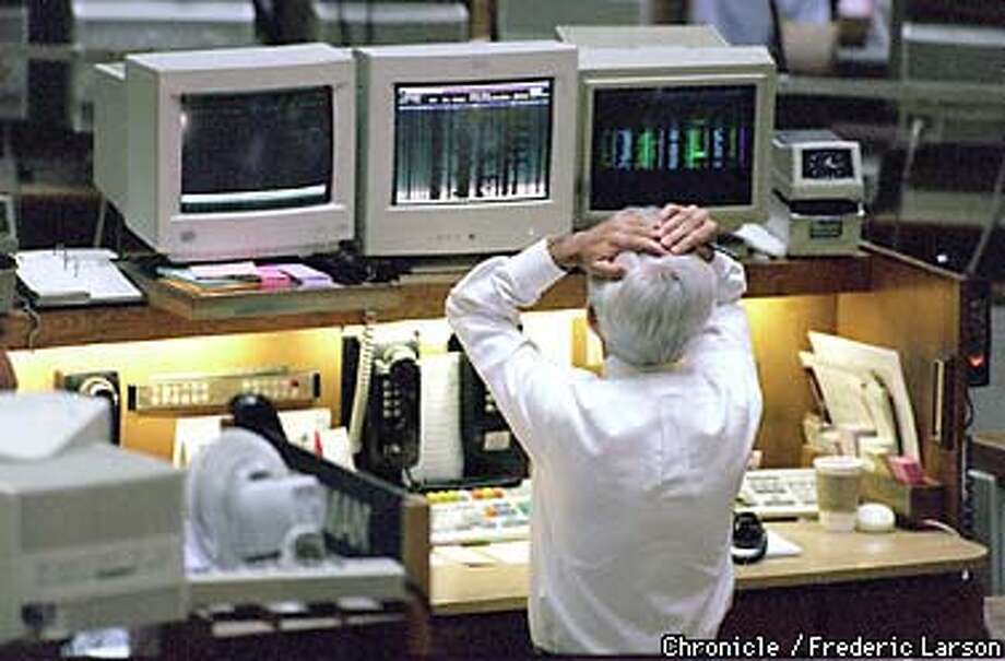 : A stock trader from the Pacific Stock exchange on Pine reviews the 512 point drop in the stock market during the closing minute of trading. Chronicle photo by Frederic Larson. Photo: Frederic Larson