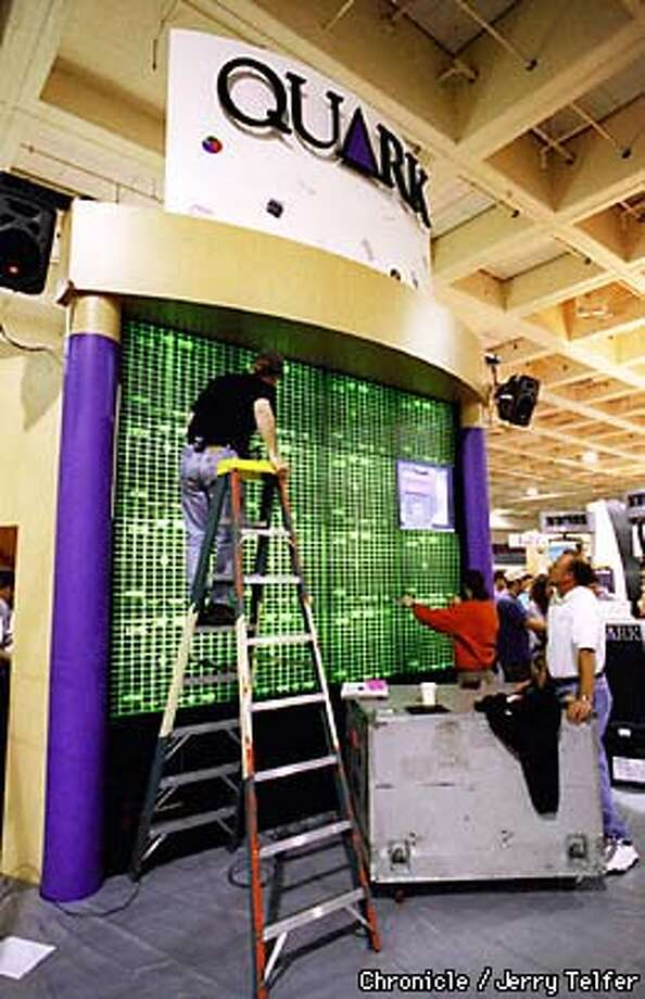 Workmen adjust giant monitor screen while setting up the Quark Corporation exhibit for the Seybold Exhibition at Moscone Center.  BY JERRY TELFER/THE CHRONICLE Photo: JERRY TELFER
