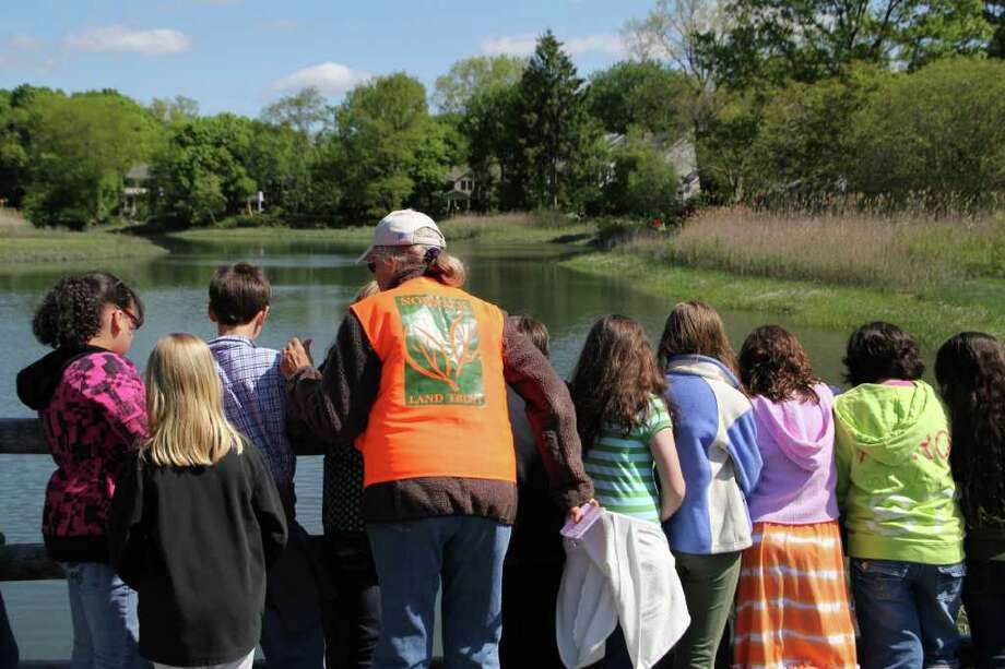 Former Norwalk Land Trust Marny Smith talks to fourth graders about the tidal estuary at Farm Creek Preserve during the NLT's outdoor classroom program. Photo: Contributed Photo