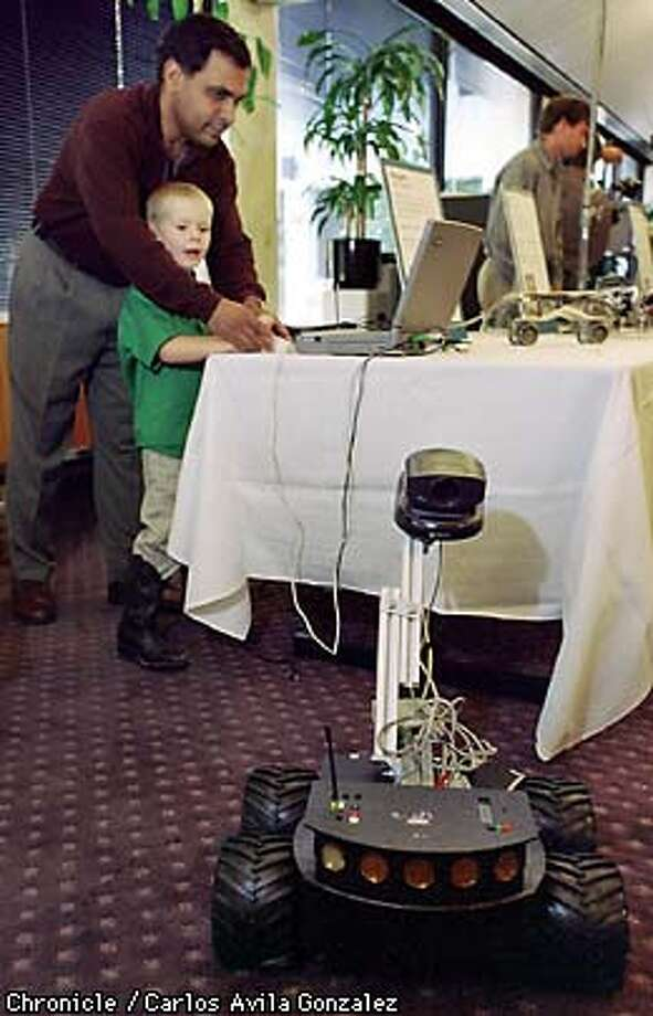 Venkat Shastri, a senior research scientist at SRI, shows Cameron McElfresh,4, how to operate the Pioneer Robot during an exposition of robotic technology at SRI International in Menlo Park on Wednesday, August 26, 1998. (CHRONICLE PHOTO BY CARLOS AVILA GONZALEZ) Photo: CARLOS AVILA GONZALEZ