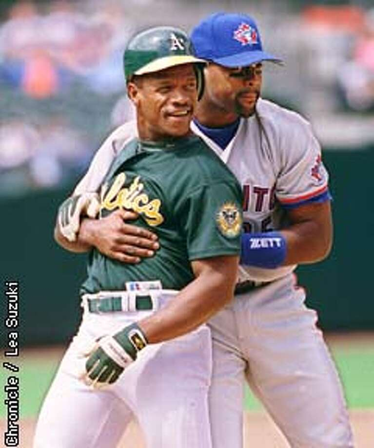 A's Rickey Henderson falls back against Carlos Delgado after scurrying back to first base to avoid being tagged out in the bottom of the seventh. PHoto By Lea Suzuki Photo: LEA SUZUKI