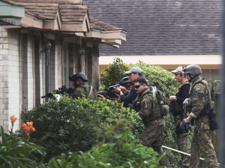 Houston SWAT officers force their way into the home of a man who was later found dead, apparently by his own hand. Decorory Pruitt, 27, had been sought Friday after a knife attack on a 4-year-old girl. Photo: Johnny Hanson, Houston Chronicle