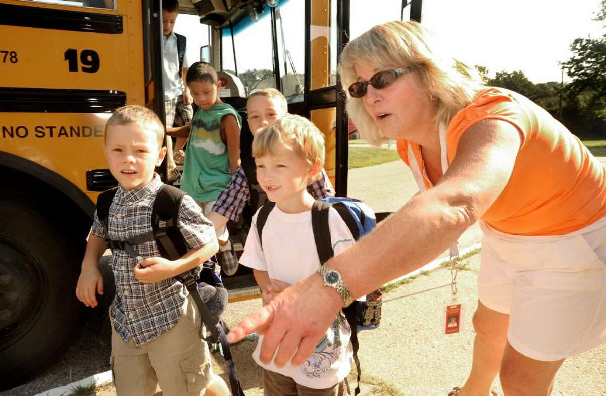 Para-educator Lori Corsak directs returning students entering John Pettibone School in New Milford for the first day of classes on Aug.26, 2009.