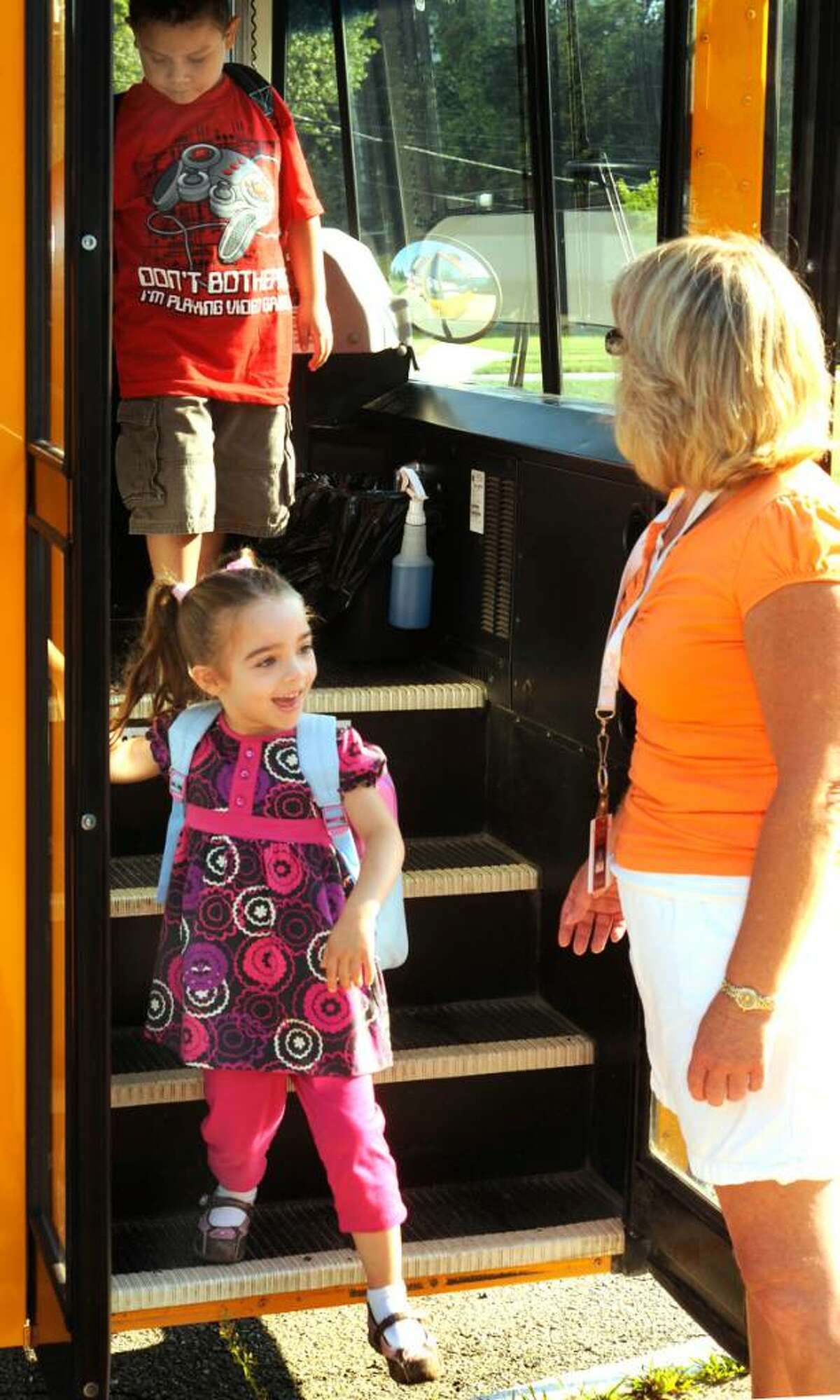Kindergarten student Felicia Crowley greets para-educator Lori Corsak as she steps off the bus for the first day of school at John Pettibone School in New Milford on Aug. 26, 2009.
