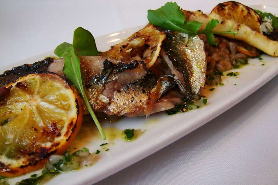 Charcoal-grilled herring with farro, grilled Meyer lemon, and salmoriglio sauce from Oliveto Restaurant and Cafe is seen on Thursday, Feb. 2, 2012 in Oakland, Calif. Photo: Teal Dudziak, Oliveto Restaurant And Cafe