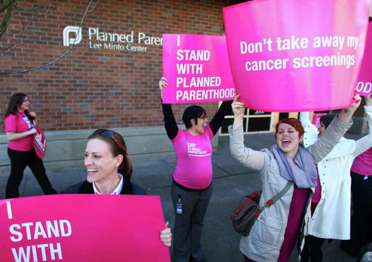Supporters of Planned Parenthood, from left, Angela Vogel, Tricia Goodwin, Mandi Moshay and Kirsten Dees hoist signs in front of the not-for-profit family planning agency on Friday, February 3, 2012 on East Madison Street in Seattle. Dozens of supporters of the organization gathered with U.S. Senator Patty Murray after the Susan G. Komen for the Cure foundation reversed a decision to suspend funding to Planned Parenthood.