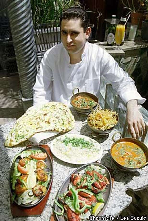 Dharampal Singh Malhi, main chef and owner's brother, with some of the dishes offered up at India Garden restaurant. Clockwise from top: Punjabi Lamb Curry (House Specialty), Hydrabadi Chicken Curry (House Specialty), Fish Tikka Masala, Tandoori Chicken, Prawn Tandoori, Garlic Nan and Pilav (rice, center). PHoto By Lea Suzuki Photo: LEA SUZUKI