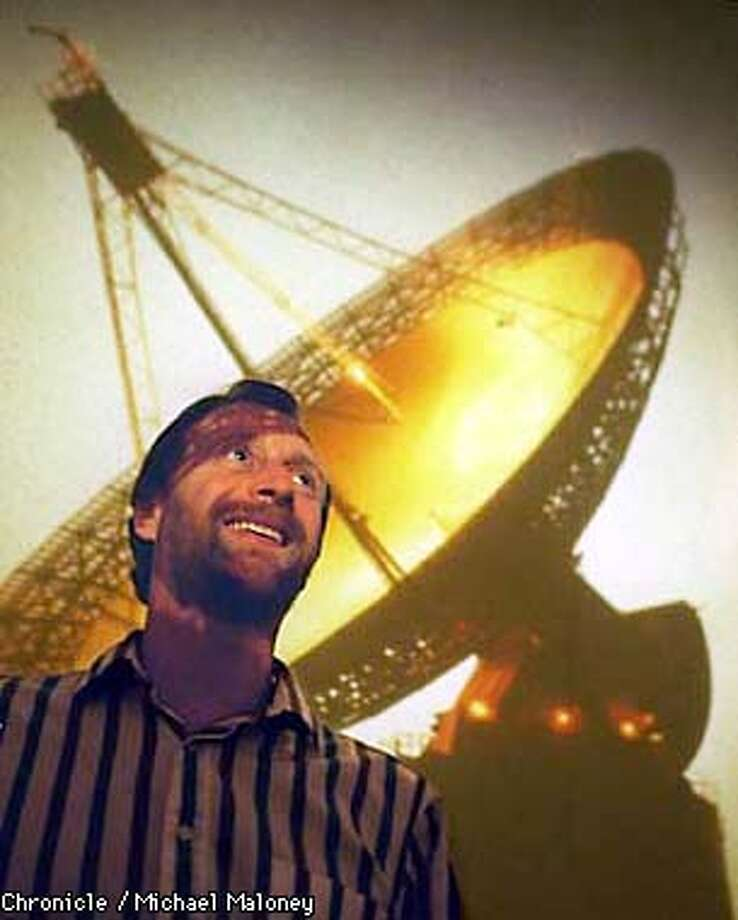 Dan Werthimer is a manager of a program at UC Berkeley searching for extra-terrestrial radio signals from outer space. The new program, Seti@Home hopes to find volunteers who will install software on their computers to help collect data from the Arecibo telescope in Puerto Rico.  Werthimer is photographed in front of a slide projection of a similar antenna dish that SETI uses in their research.  Photo by Michael Maloney Photo: MICHAEL MALONEY