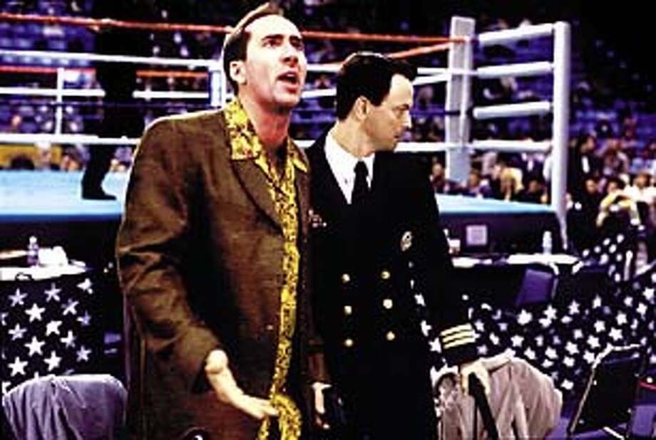 A con-man detective (Nicholas Cage), with his Navy pal (Gary Sinise), helps to investigate a murder at championship boxing match in Brian De Palma's ``Snake Eyes.''.