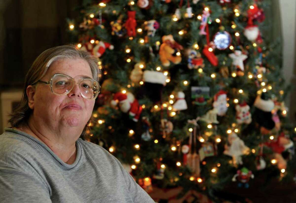 """Giants fan Lynn Ramos poses in front of her Christmas tree at her home in Bridgeport, Conn. on Wednesday February 1, 2012. She and her son Bobby decided to leave the tree up because it was """"good luck"""" for the team. They won't take it down until after the superbowl."""