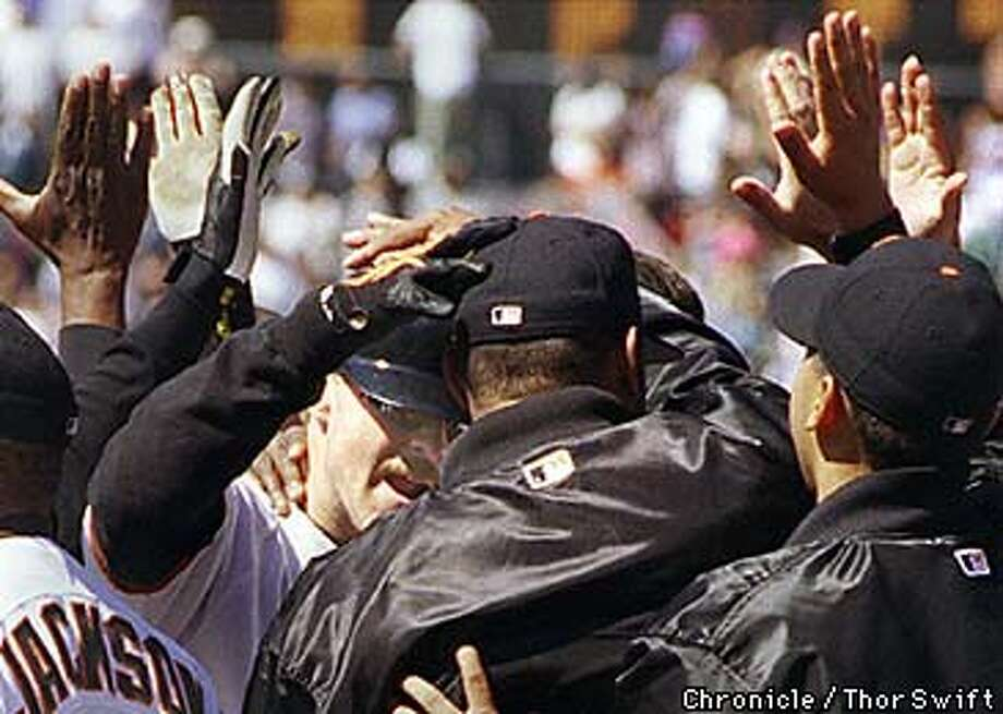 The Giants' Jeff Kent is surrounded by teamates as he crosses home after hitting a tenth inning home run against the Cincinnati Reds, Sunday, July 16, 1998, in San Francisco.  BY THOR SWIFT/THE CHRONICLE Photo: THOR SWIFT