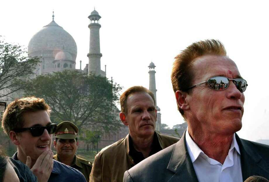 Austrian born Hollywood star and former Governor of California Arnold Schwarzenegger, right, stands in front of the historic Taj Mahal, in Agra, India, Friday, Feb. 3, 2012. Schwarzenegger, who is in the country attending a conference, was unable to visit the inside of the compound of the world famous site as it is closed Fridays. (AP Photo/Pawan Sharma) Photo: Pawan Sharma