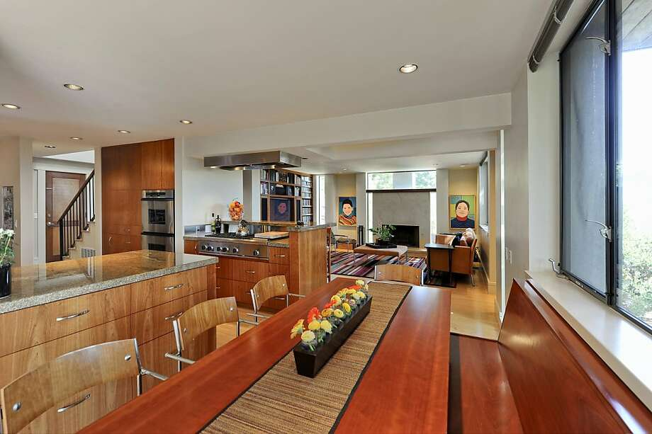 The kitchen has stainless steel appliances and flows to a casual dining area, with bench seating, and the family room. Photo: Thomas Grubba Photography