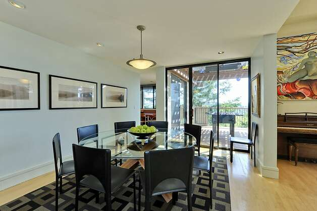 This bright dining room receives ample natural light and offers access to the living room and outdoor deck. Photo: Thomas Grubba Photography