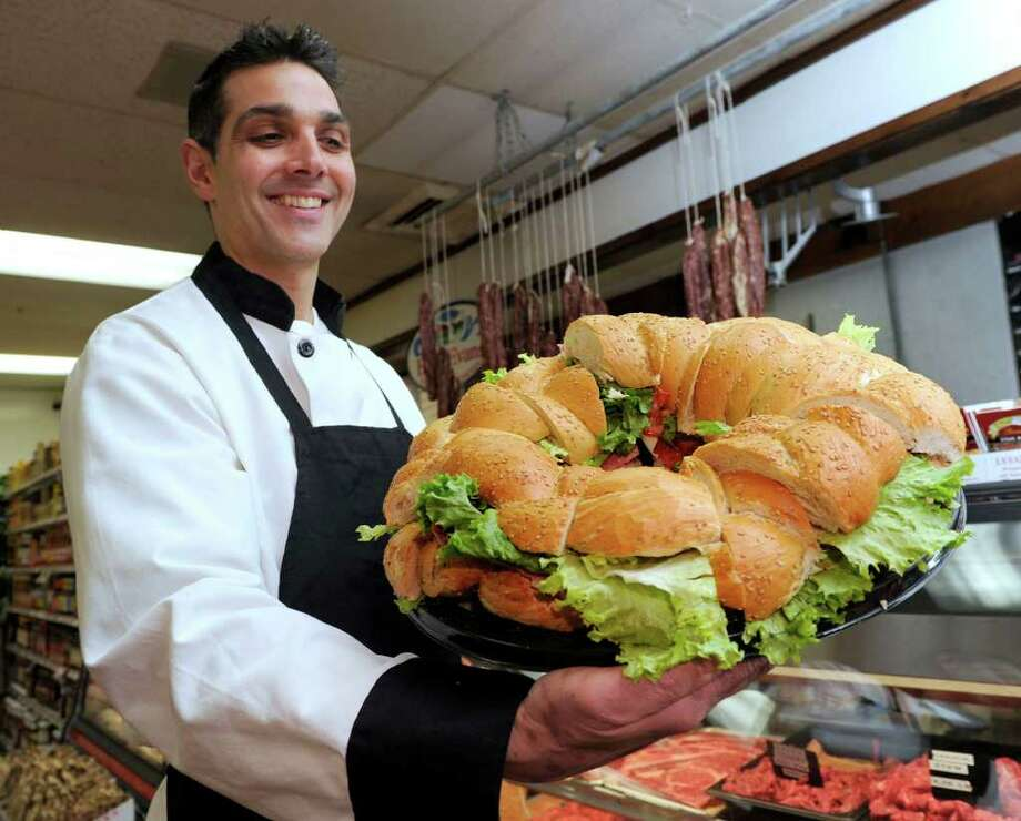 Johnny Petrone, 46, owner of the Johnny's New Fairfield Food Center and  Catering, holds a three-foot round deli sandwich, one of the popular items he'll be making for customers for Super Bowl Sunday. Photo taken Wednesday, Feb. 1, 2012. Photo: Carol Kaliff / The News-Times