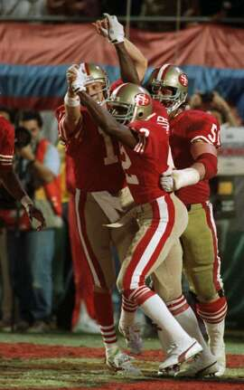 San Francisco 49ers quarterback Joe Montana (16) and wide receiver John Taylor (82) clasp hands after Montana's pass to Taylor at the end of the fourth quarter resulted in a 20-16 victory over the Cincinnati Bengals at Super Bowl XXIII Jan.22, 1989 in Miami. (AP Photo/Rusty Kennedy)