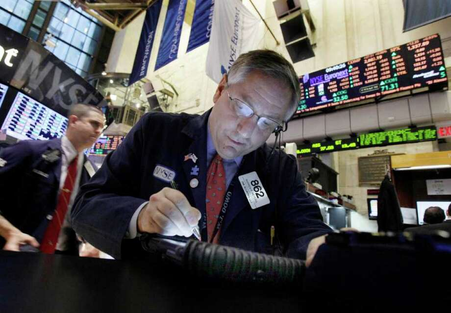 Trader Warren Meyers, right, is illuminated by his handheld device as he works on the floor of the New York Stock Exchange Friday, Feb. 3, 2012. U.S. stocks are opening sharply higher after the unemployment rate dropped to the lowest in two years. (AP Photo/Richard Drew) Photo: Richard Drew
