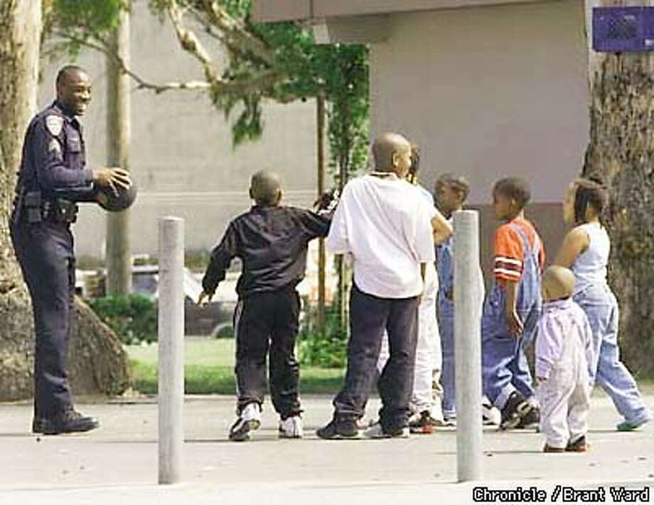 """""""James Gordon"""", a security guard at the Alemany husing project, organized a basketball game with some young residents. The kids love to play with james. Photo: Brant Ward"""