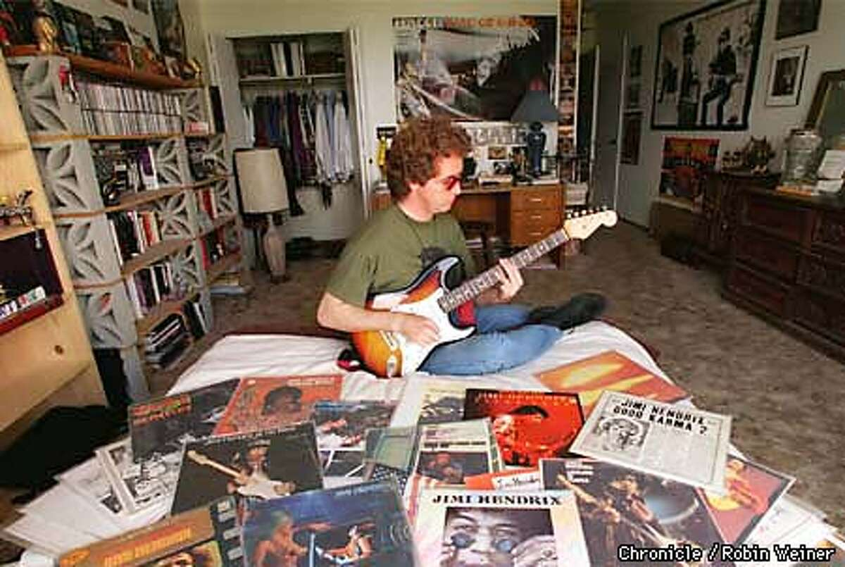 Keith Dion plays his guitar surrounded by Jimi Hendrix record albums, posters and other items he collects in his Sunset District apartment. Robin Weiner/The Chronicle