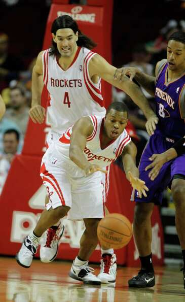 Houston's Kyle Lowry (7) and Luis Scola (4) chase down a loose ball during the first half of an NBA