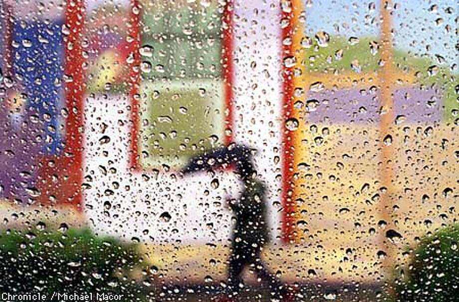 Raindrops collect on a window in downtown Concord off Salvio St. as a passerby with an umbrella walks in front of a colorfull building mural. By Michael Macor/The Chronicle Photo: MICHAEL MACOR