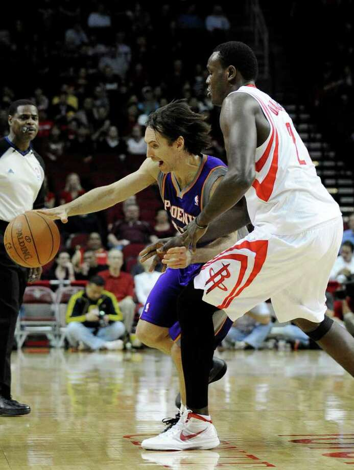 Phoenix Suns' Steve Nash, left, is pressured by Houston Rockets' Samuel Dalembert, right, in the first half of an NBA basketball game Friday, Feb. 3, 2012, in Houston. (AP Photo/Pat Sullivan) Photo: Pat Sullivan, Associated Press / AP