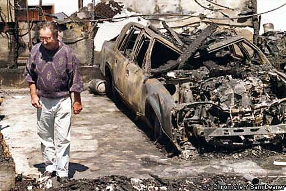 Wallace Galbraith looked through charred debris around his 1988 Town car in what was formerly his garage at his home on Yukon Street in Concord. An explosion ripped through the garage early Tuesday morning and fire destroyed the house. A propone tank believed to be a source of the fire rests next to the car's rear tire. No one was injured. (Chronicle Photo by Sam Deaner) Photo: SAM DEANER