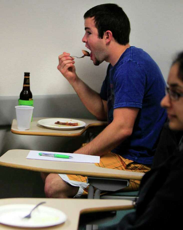 "Jonathan Hammann, 21, eats barbecue and drinks a beer in ""Kickin' It in Small Town Texas"" a Rice University class that looks at life ""beyond the hedges."" Photo: Mayra Beltran / © 2012 Houston Chronicle"