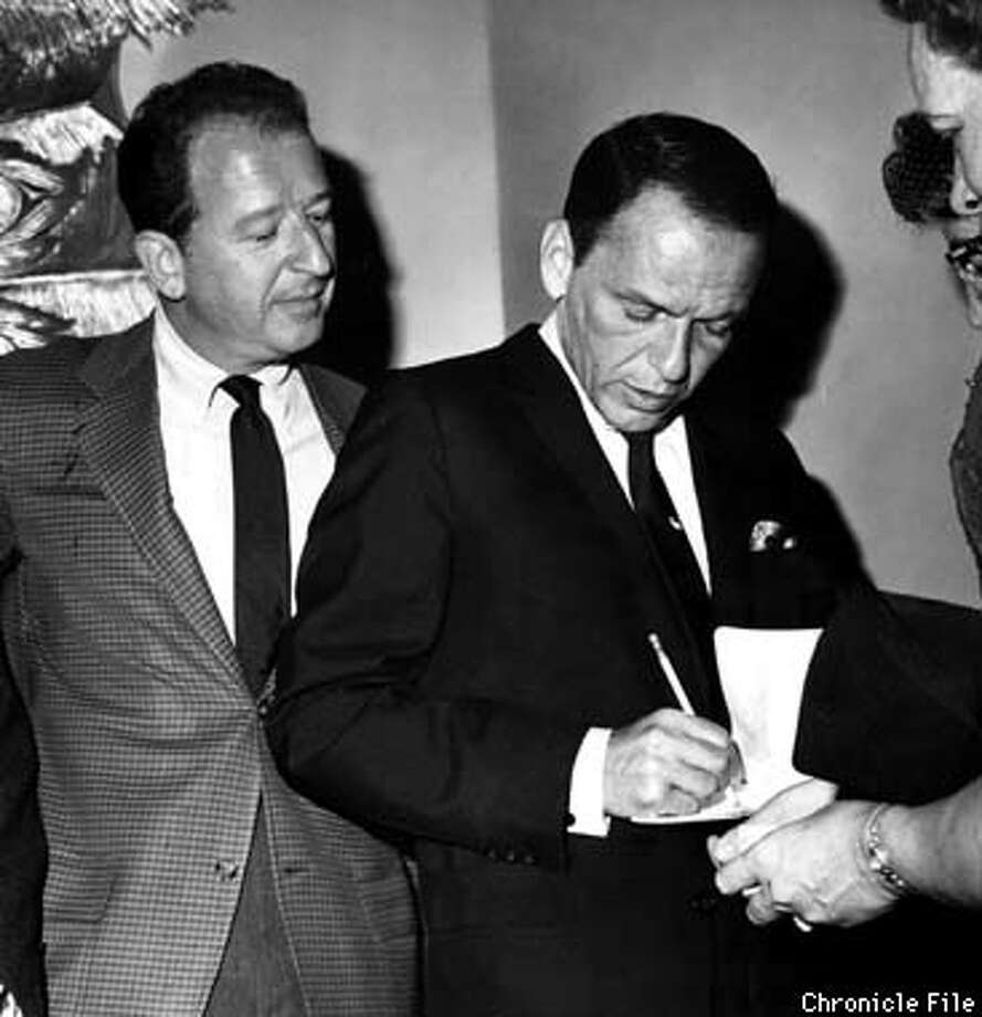 """""""The fellow at the right who looks like Frank Sinatra signing an autograph is Frank Sinatra signing an autograph and making rather a hard job of it. This was taken in the Mark Hopkins Hotel lobby around 1955, I would guess, when Frank and I were buddies. I am saying something hilarious, like """"Frank Sinatra? I thought you were Perry Como.'"""" -- The Chronicle's late, great columnist Herb Caen, taking a turn at caption-writing. Chronicle File Photo"""