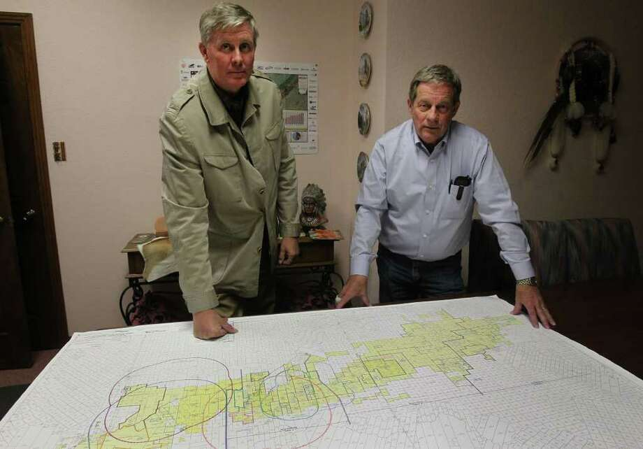Geologist Gregg Robertson (left) worked with people at Petrohawk Energy in Houston and their discovery in La Salle county turned out to be a historic find: the Eagle Ford shale formation. Standing (right) with Robertson is Robert Graham, a landman who helped put together leased acreage on the Eagle Ford area. On the table is a map of the Eagle Ford area. Photo: SAN ANTONIO EXPRESS-NEWS