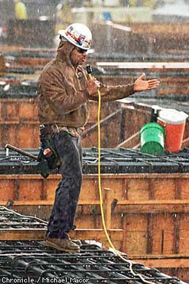Rain storms hit the Bay Area Tuesday afternoon. Carpenter Joe Cartagena working the Pacific Bell Ball Park Project about to wrap up work for the day due to the rain. Here he sings into an eletrical cord as the rain falls around him. By Michael Macor/The Chronicle Photo: MICHAEL MACOR
