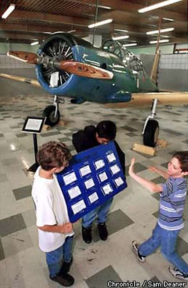 Mike Evans, right, gallantly makes a selection while playing Bryan Calidonna, left, and Andrew Martinez's traveling exhibit game board, Question Air, as part of Space a Day and Beyond at Travis Air Museum Thursday. Question Air is a trivia game about famous aviators.  Evans and Calidonna are 5th-graders at Travis Elementary and Martinez is a 5th-grader at Center Elementary. (Chronicle Photo by Sam Deaner) Photo: SAM DEANER