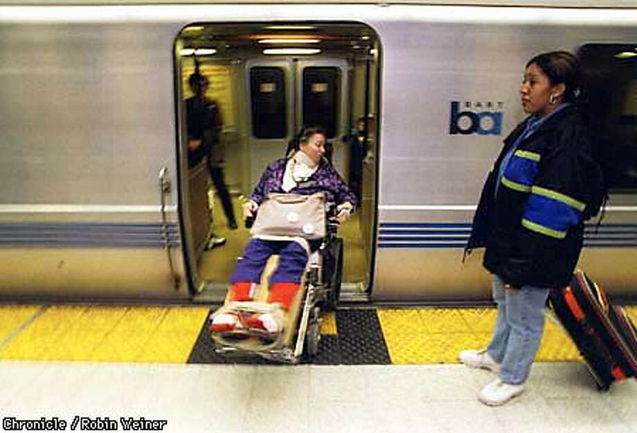 Jean Nandi, center maneuvers her wheelchair onto a BART train while an unidentified woman, right, waits to board at the 19th Street BART station in Oakland. Disability Advocates has settled a class action lawsuit with BART to improve access for riders with disabilities. Robin Weiner/The Chronicle