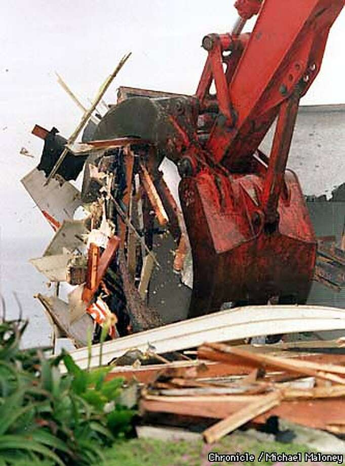 A giant claw crumbles a section of house along Esplanade Drive in Pacifica.  Seven red-tagged homes were demolished this morning along Esplanade Drive in Pacifica as neighbors and former residents watched. The homes were in danger of falling over the weather eroded ocean cliffs so officials ordered the demolition.  Photo by Michael Maloney Photo: MICHAEL MALONEY