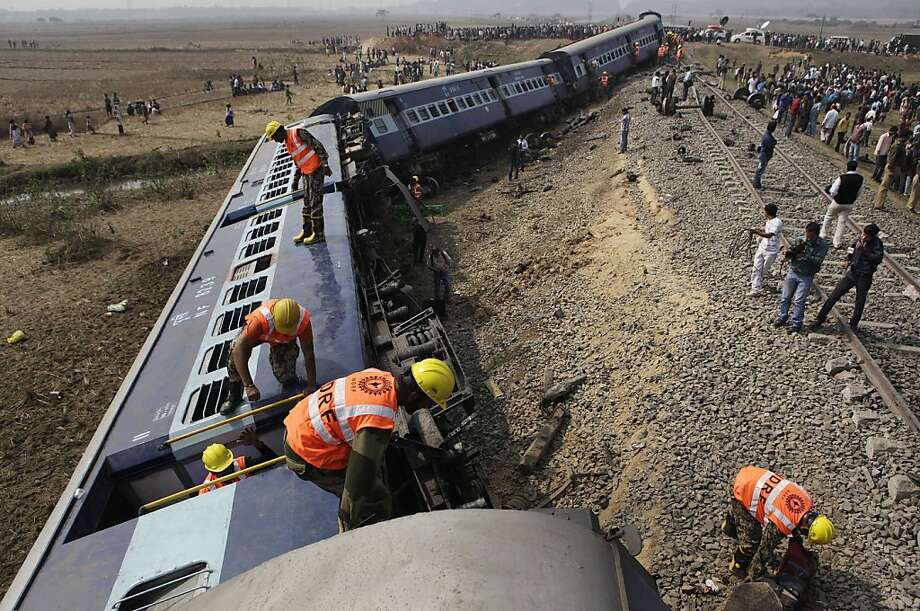 Indian disaster response personnel search as onlookers gather around derailed cars of a passenger train following an accident at Sathi Sarapa village near Gauhati, India, Friday, Feb. 3, 2012. A railway official said the train hit a bulldozer and derailed at an unmanned crossing in the north-eastern Indian state. (AP Photo/Anupam Nath) Photo: Anupam Nath, Associated Press