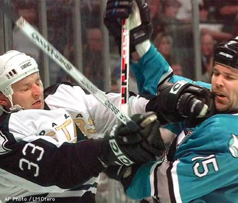 San Jose Sharks' John MacLean (15) trades blows with Dallas Stars' Benoit Hogue (33 ) during the first period of their NHL playoff game in Dallas, Thursday, April 30, 1998. (AP Photo/LM Otero) Photo: LM OTERO