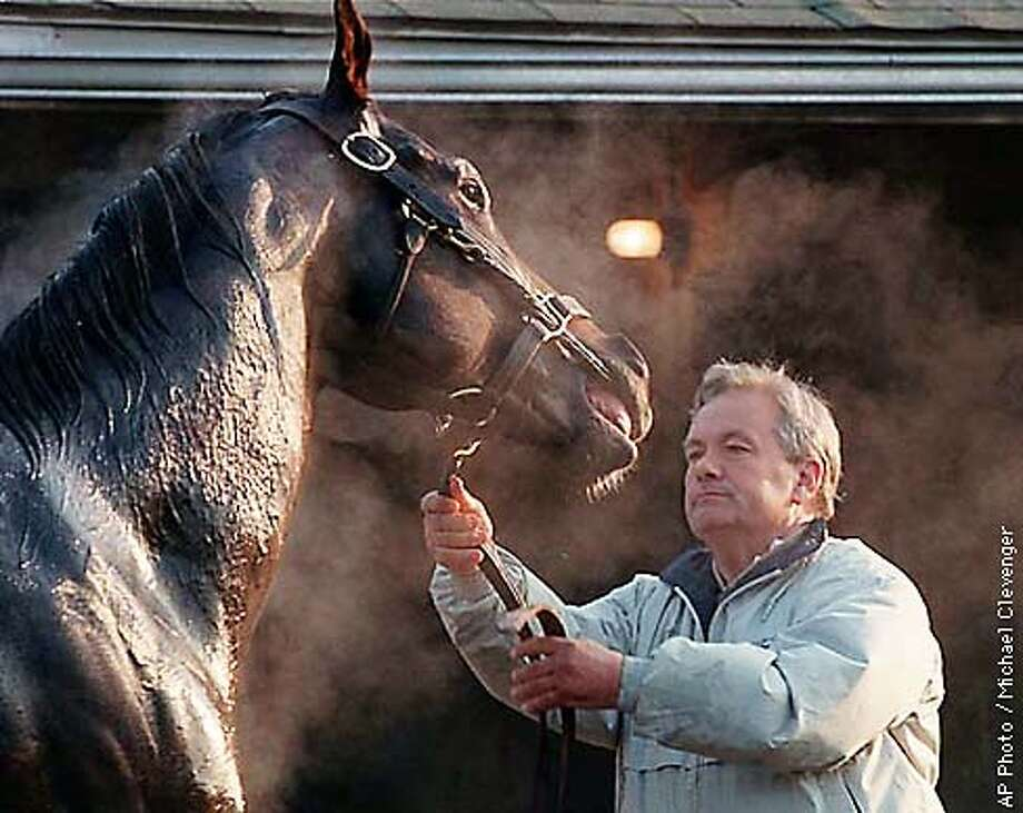 Trainer Jerry Hollendorfer holds Event of the Year as the horse is bathed after an early morning workout Thursday, April 23, 1998 at Churchill Downs in Louisville, Ky. Event of the Year broke a bone in his right front knee during a workout today at Churchill Downs and is now out of the Kentucky Derby. (AP Photo/Michael Clevenger) Photo: MICHAEL CLEVENGER