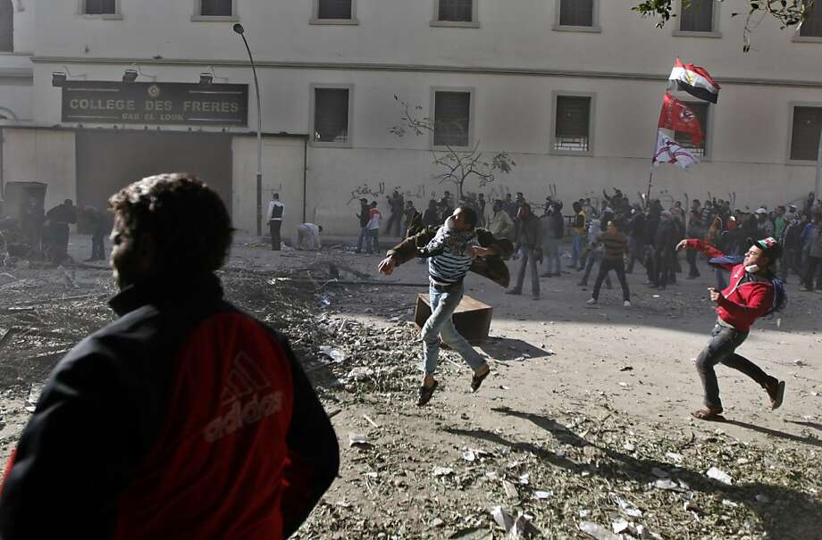 Egyptian protestors throw stones during clashes with security forces near the Interior Ministry in Cairo, Egypt, Friday, Feb. 3, 2012. Police in Cairo fired salvos of tear gas and birdshot Friday at rock-throwing protesters as popular anger over a deadly soccer riot spilled over into a second day of street violence that left three people dead and more than 1,500 injured, doctors and health officials said. Photo: Khalil Hamra, Associated Press