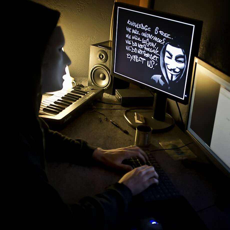 """A masked hacker, part of the Anonymous group, hacks the French presidential Elysee Palace website in this January 20, 2012 file photo near the eastern city of Lyon.   Hacker group Anonymous, in an embarrassment for law enforcement, released a recording on February 3, 2012 of a conference call between the FBI and Scotland Yard discussing operations against the hacking collective. The Federal Bureau of Investigation confirmed the authenticity of the nearly 17-minute recording posted on YouTube and other sites and said it was """"intended for law enforcement officers only and was illegally obtained. """"A criminal investigation is under way to identify and hold accountable those responsible,"""" the FBI said in a statement. Photo: Jean-Philippe Ksiazek, AFP/Getty Images"""